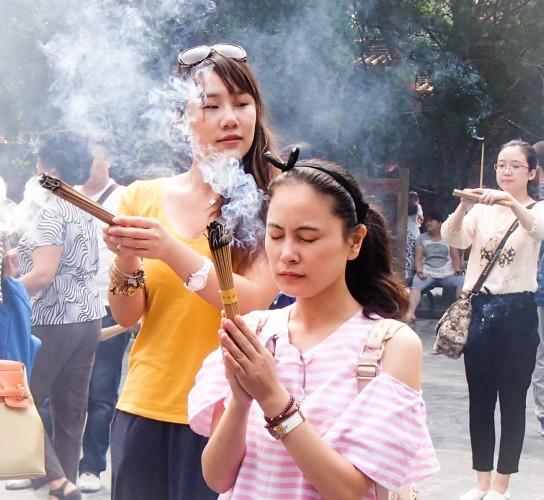 Jeunes filles en prière au temple des Lamas