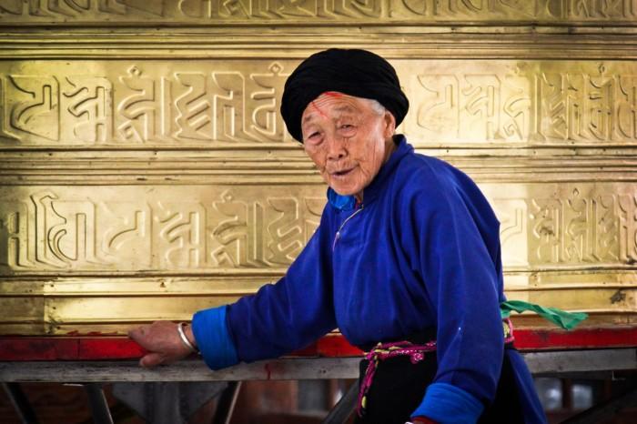 Une habitante de Kangding et un moulin à prières